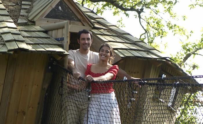 A Dihan, devant une cabane perchée dans les arbre, Myriam et Arno.